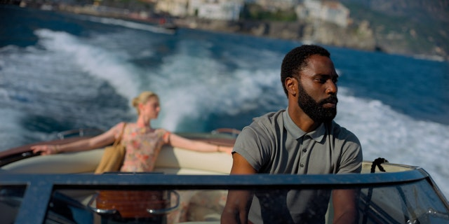 This image released by Warner Bros. Entertainment shows Elizabeth Debicki, left, and John David Washington in a scene from 'Tenet.' (Melinda Sue Gordon/Warner Bros. Entertainment via AP)