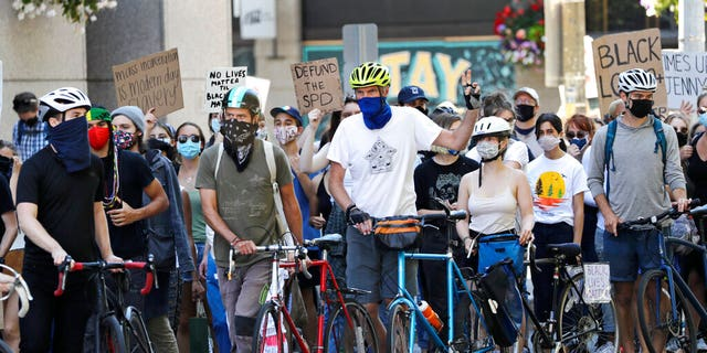 Bicyclists maintain a line to help protect marchers from traffic during a protest led by youth activists demanding racial, climate, economic, worker, and social justice Monday, July 20, 2020, in Seattle. The demonstration follows other protests over the death of George Floyd, a Black man who was in police custody in Minneapolis.