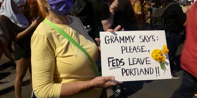 Mardy Widman, a 79-year-old grandmother of five, protests the presence of federal agents outside the Mark O. Hatfield Federal Courthouse in Portland, Ore., Monday, July 20, 2020. (AP Photo/Gillian Flaccus)