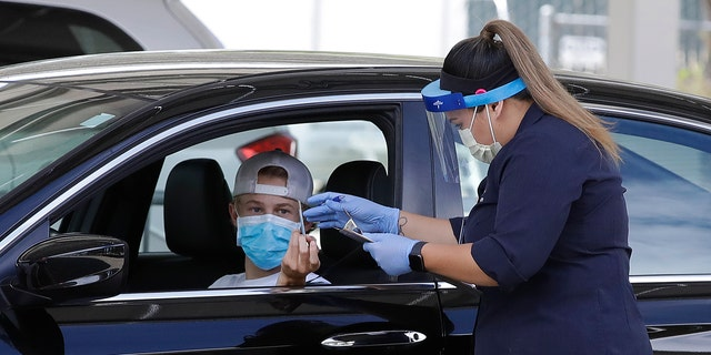 A healthcare worker takes information from a person at a Covid-19 testing center on Tuesday, July 21, 2020, in Pleasanton, Calif. (AP Photo/Ben Margot)