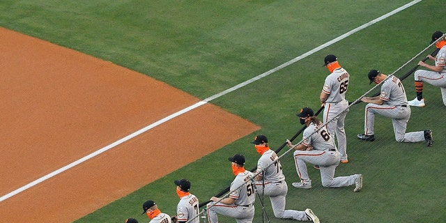 Most members of the San Francisco Giants kneel during a moment of silence prior to an opening day baseball game against the Los Angeles Dodgers, July 23, in Los Angeles. (AP Photo/Mark J. Terrill)