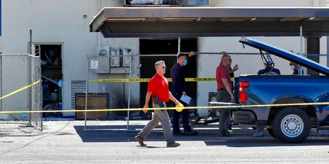 Fire investigators stand outside the Arizona Democratic Party headquarters Friday, July 24, 2020, in Phoenix. (Associated Press)