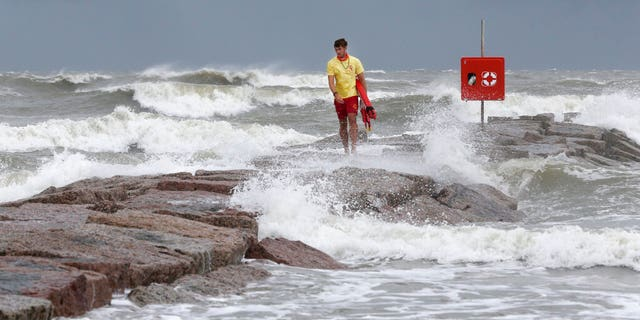 Galveston Island Beach Patrol lifeguard Matthew Herdrich walks along the rock groin at 39th Street in Galveston, Texas, as waves kicked up by Tropical Storm Hanna wash over it Friday, July 24, 2020. Officials in South Texas say they're prepared to handle any challenges from Tropical Storm Hanna. The storm is headed their way and expected to make landfall this weekend. (Jennifer Reynolds/The Galveston County Daily News via AP)