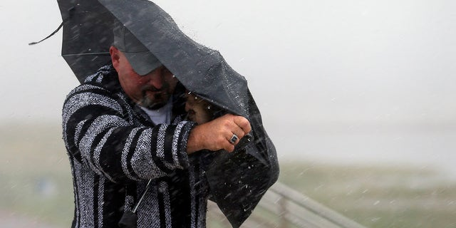 A man holds the front on his umbrella as he fights heavy rain and wind on Seawall Boulevard in Galveston, Texas, Saturday, July 25, 2020. (Associated Press)