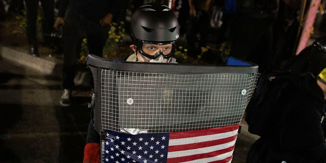 A protester holds a homemade riot shield during a protest in front of the Oakland Police Department Station on Saturday, July 25, 2020, in Oakland, Calif. (Associated Press)