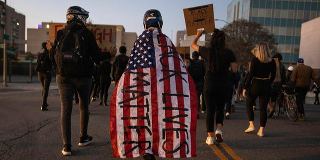 "A protester wrapped in an American flag spray painted with ""Black Lives Matter"" marches down a street during a protest on Saturday, July 25, 2020, in Oakland, Calif. (Associated Press)"