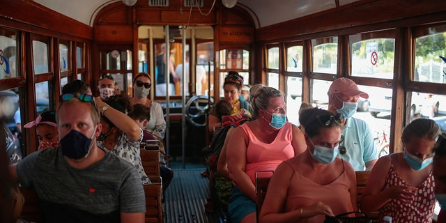 Tourists and locals ride a tram in town of Sóller in the Balearic Island of Mallorca, Spain, Monday, July 27, 2020. Britain has put Spain back on its unsafe list and announced Saturday that travelers arriving in the U.K. from Spain must now quarantine for 14 days. (AP Photo/Joan Mateu)