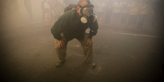 A demonstrator is wearing a gas mask when federal officers deploy tear gas during a protest at the Black Lives Matter against Mark O. Hatfield, the U.S. Courthouse in Portland, Ore, and several police departments in Wisconsin have refused to send officers to the Democratic National Convention.  in response to local regulations preventing the use of tear gas to control the crowd.