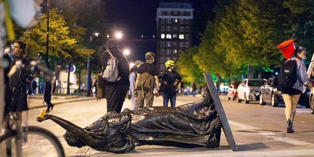 """In this June 23, 2020 file photo, Wisconsin's """"Forward"""" statue lies in the street on Capitol Square in Madison, Wis. Crowds outside the Wisconsin State Capitol tore down two statues and attacked a state senator amid protests following the arrest of a Black man who shouted at restaurant customers through a megaphone while carrying a baseball bat. (Emily Hamer/Wisconsin State Journal via AP, File)"""