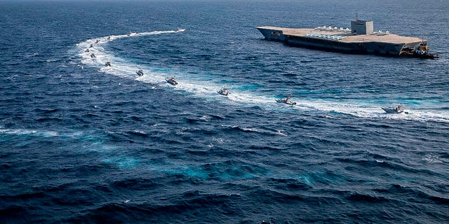 The speedboats of the Revolutionary Guard orbit a replica of an American air carrier during a military exercise.  (Sepahnews via AP)