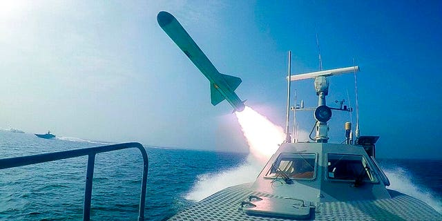 Revolutionary Guard's speed boat fires a missile during a military exercise. Iranian commandos also fast-roped down from a helicopter onto a replica of an aircraft carrier in the exercise called