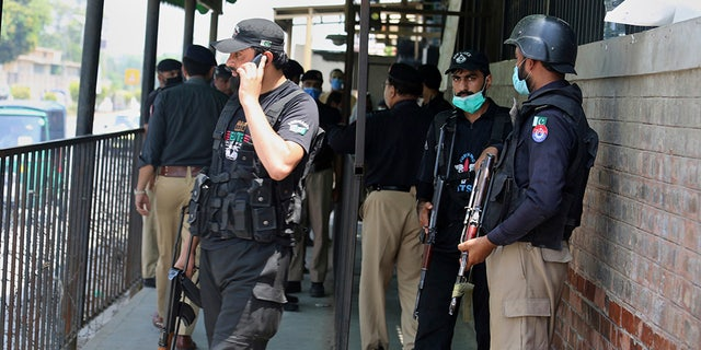 Police gather at the entrance gate of the district court after the killing of Tahir Ahmad Naseem, who was accused in court of insulting Islam, in Peshawar, Pakistan, on Wednesday, July 29, 2020. (AP Foto / Muhammad Sajjad)