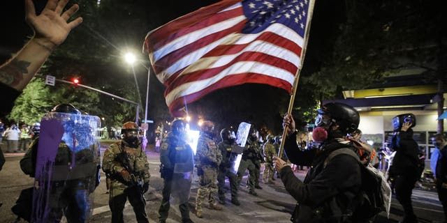 election 2020  Donald Trump  President Trump  Conservative News  RNC A demonstrator waves a U.S. flag in front of federal officers after tear gas is deployed during a Black Lives Matter protest at the Mark O. Hatfield United States Courthouse July 30, in Portland, Ore. (AP Photo/Marcio Jose Sanchez)