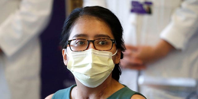 Mayra Ramirez, a COVID-19 survivor due to a double-lung transplant, listens Thursday, July 30, 2020, to a question about her journey through the pandemic during her first news conference at Northwestern Memorial Hospital in Chicago. Ramirez is the first known patient in the United States who received double-lung transplants due to COVID-19. (AP Photo/Charles Rex Arbogast)