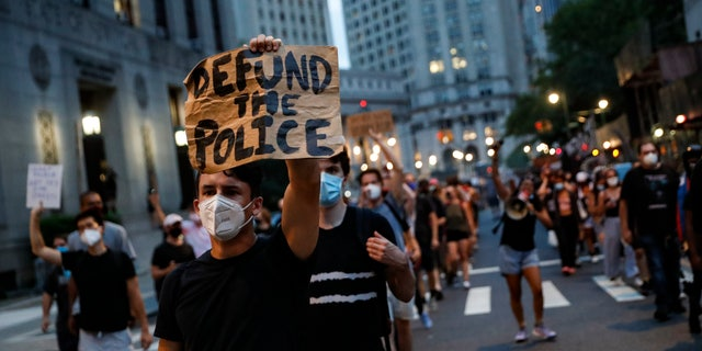 "A demonstrator holds a sign that reads ""Defund the police"" during a protest march in support of the Black Lives Matter movement and other groups, Thursday, July 30, 2020, in New York. (AP Photo/John Minchillo)"