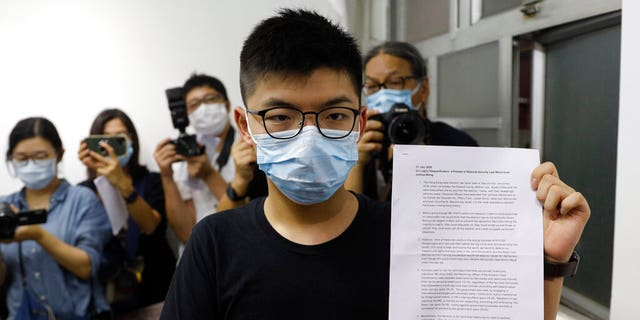 Hong Kong pro-democracy activist Joshua Wong shows his disqualification notice during a press conference in Hong Kong, July 31. (AP Photo/Kin Cheung)