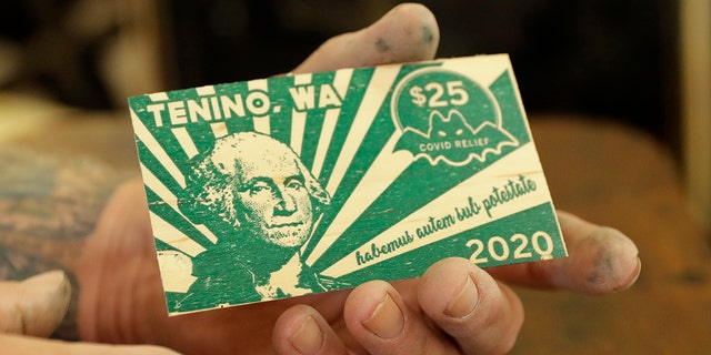 In an effort to help residents and local merchants alike get through the economic fallout of the coronavirus pandemic, the small town has issued wooden currency for residents to spend at local businesses, decades after it created a similar program during the Great Depression. (AP Photo/Ted S. Warren)