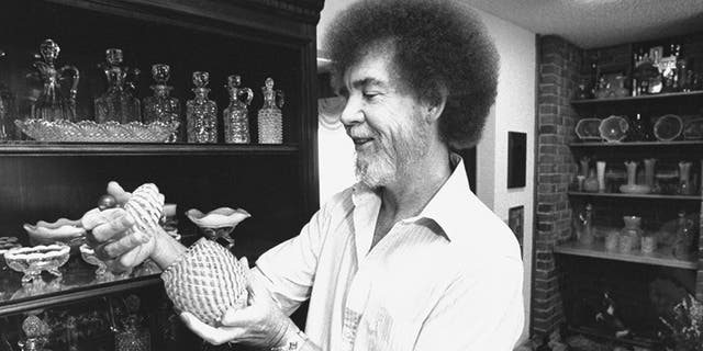 TV painting instructor/artist Bob Ross examining a piece from his collection of turn-of-the-century Victorian opalescent glass next to a cabinet full of decanters & dishes at home.