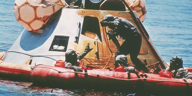U.S. Navy personnel, protected by Biological Isolation Garments, are recovering the Apollo 11 crew from a re-entry vrehicle, which landed safely in the Pacific Ocean on July 24, 1969, after an eight-day mission on the moon. (AP Photo)