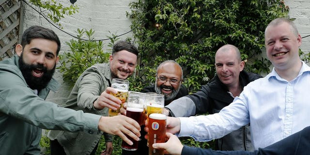 Men enjoy their first beers as the Chandos Arms pub reopens, in London, Saturday, July 4, 2020. England is embarking on perhaps its biggest lockdown easing yet as pubs and restaurants have the right to reopen for the first time in more than three months. In addition to the reopening of much of the hospitality sector, couples can tie the knot once again, while many of those who have had enough of their lockdown hair can finally get a trim.