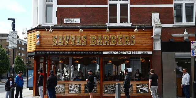 People queue outside Savvas Barbers as it reopened following the outbreak of the coronavirus disease (COVID-19), in London, Britain July 4, 2020. REUTERS/Hannah McKay - RC28MH94GQPU