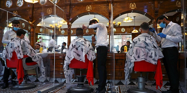 Men have their hair cut at Savvas Barbers as it reopened following the outbreak of the coronavirus disease (COVID-19), in London, Britain July 4, 2020. REUTERS/Hannah McKay - RC29MH9YHVPQ