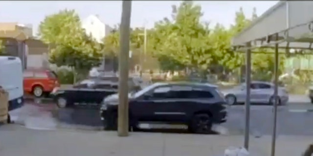 Image from video showing a hooded figure firing a weapon towards a New York City playground basketball court as he hangs out of the sunroof of an SUV.