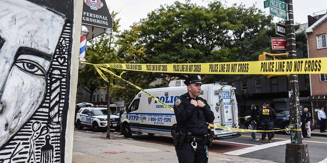 An NYPD officer stands nearby as a crime scene is established in front of the Triple-A Aces social club on Utica Avenue on October 12, 2019 in New York City. (Stephanie Keith/Getty Images)