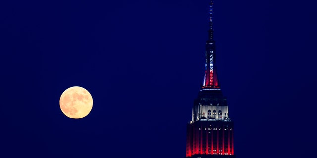 The moon rises to go to the Empire State Building in front of Macy's Fourth of July Fireworks Spectacular July 4, 2020 in New York City.