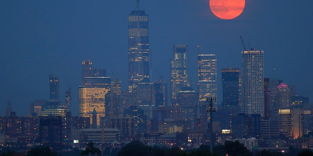 On the 50th anniversary of the launch of Apollo 11, the full buck moon rises above the skyline of lower Manhattan and One World Trade Center in New York City on July 16, 2019 as seen from Kearney, New Jersey - file photo.