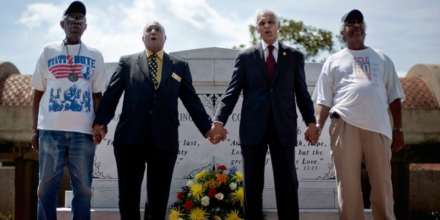 """FILE - In this April 4, 2012 photo, civil rights activists and Southern Christian Leadership Conference members, from left, Ralph Worrell, Dr. Bernard Lafayette, Jr., C.T. Vivian and Frederick Moore, join hands and sing """"We Shall Overcome"""" at the Atlanta gravesite of Rev. Martin Luther King Jr., marking the 44th anniversary of his assassination. The Rev. Vivian, a civil rights veteran who worked alongside the Rev. Martin Luther King Jr. and served as head of the organization co-founded by the civil rights icon, has died at home in Atlanta of natural causes July 17, his friend and business partner Don Rivers confirmed to The Associated Press. Vivian was 95. (AP Photo/David Goldman, File)"""