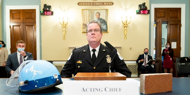 Acting U.S. Park Police Chief Gregory T. Monahan, testifies before a House Natural Resources Committee hearing on actions taken on June 1, 2020 at Lafayette Square, Tuesday, July 28, 2020 on Capitol Hill in Washington. He sits with a helmet of one of the officers who was injured by a violent protester who threw a brick at his head. (Bill Clark/Pool via AP)