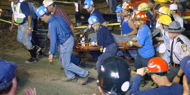 Pennsylvania Gov. Mark Schweiker, left, helps carry out the last of the trapped miners at the Quecreek Mine in Somerset, Pa., Sunday July 28, 2002. (AP Photo/Steve Helber/POOL)
