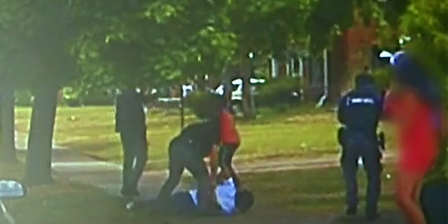 Police footage show officers arresting Darnell Sylvester moments before his friend, Hakeem Littleton (in orange shirt) opens fire on officers.