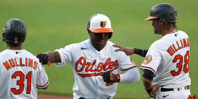 Baltimore Orioles' Dilson Herrera, center, is greeted by Cedric Mullins, left, and Mason Williams after he hit a three-run home run during an intrasquad game at baseball training camp Tuesday, July 14, 2020, in Baltimore. (AP Photo/Julio Cortez)