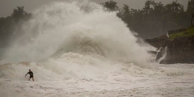 A surfer takes on a wave generated by Hurricane Douglas at Laie Beach Park, Sunday, July 26, 2020, in Laie, Hawaii.