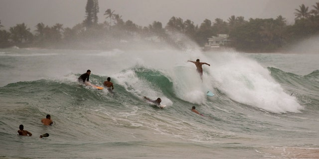 Surfers take on large waves generated by Hurricane Douglas at Laie Beach Park, Sunday, July 26, 2020, in Laie, Hawaii.