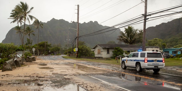 A police officer with the Honolulu Police Department inspects the sand and debris washed onto a closed portion of Kamehameha Highway, Sunday, July 26, 2020, in Kaaawa, Hawaii.