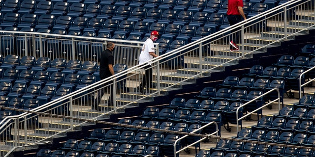 Director of the National Institute of Allergy and Infectious Diseases Dr. Anthony Fauci, center, walks through empty stands after throwing out the ceremonial first pitch at Nationals Park before the New York Yankees and the Washington Nationals play an opening day baseball game, Thursday, July 23, 2020, in Washington. (AP Photo/Andrew Harnik)
