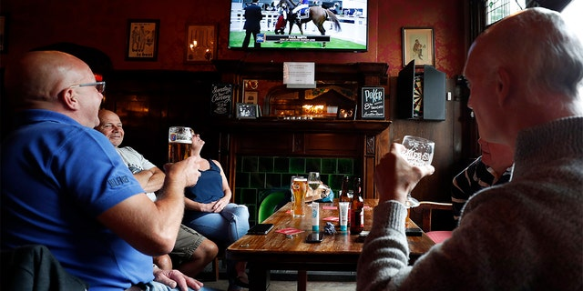 People enjoy their beers as they watch horse racing at the Forester pub in London, Saturday, July 4, 2020. England is embarking on perhaps its biggest lockdown easing yet as pubs and restaurants have the right to reopen for the first time in more than three months. In addition to the reopening of much of the hospitality sector, couples can tie the knot once again, while many of those who have had enough of their lockdown hair can finally get a trim. (AP Photo/Frank Augstein)