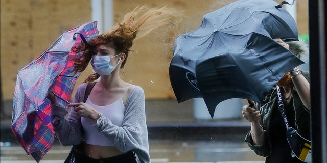 Pedestrians struggle to control their umbrellas due to inclement weather brought about by Tropical Storm Fay, Friday, July 10, 2020, in New York.