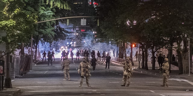 Authorities gather in the street amid protests in Portland. Ore.