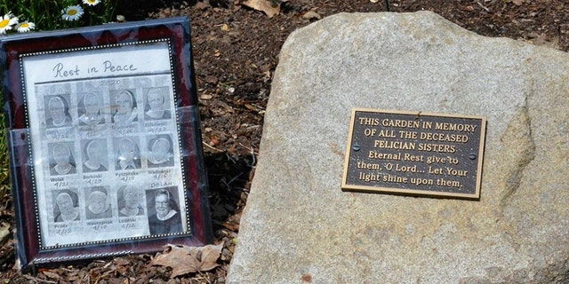 A small memorial to the 12 sisters who died in one month from COVID-19 sits in the gardens outside the Felician Sisters' convent in Livonia, Mich.