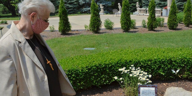 Local minister Sr. Mary Andrew Budinski looks at the memorial to remember the 12 sisters who died in one month from COVID-19 that sits in the gardens outside the Felician Sisters' convent in Livonia, Michigan.