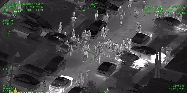 Screenshot from overhead footage of supposed 'COVID-19' party showing police arriving to disperse the party.