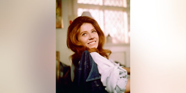Patty Duke, US actress, smiling as she turns her head toward the camera for a portrait, while sitting in a chair with a denim jacket on the backrest, circa 1970.