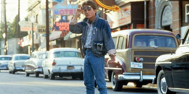 Michael J Fox walking across the street in a scene from the film 'Back To The Future', 1985.