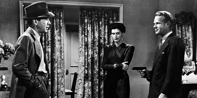 American actors (left - right): Humphrey Bogart, Sonia Darrin, and Louis Jean Heydt (1905 - 1960) in a still from the film, 'The Big Sleep,' directed by Howard Hawks, 1946.