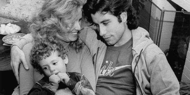 Actor John Travolta w. his arm around actress girlfriend Diana Hyland and her young son Zachary, 4, while sitting together at home.