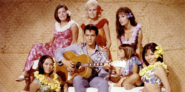 American singer and actor Elvis Presley surrounded by Linda Wong, Julie Parrish, Suzanna Leigh, Marianna Hill, Donna Butterworth (little girl), and Irene Tsu, on the set of 'Paradise, Hawaiian Style' directed by Canadian Michael D. Moore.